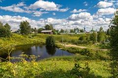 Klassiskt ryskt lantligt landskap med en kloster nära byn Fotografering för Bildbyråer