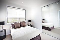 Klassiskt sovrum med fönster och lampor bredvid en spegel Arkivbild