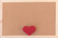 Klassiskt vanligt brunt korkbräde med röd sticka hjärta i botten av ramen royaltyfria foton