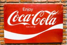 Klassiskt varumärke som brännmärker logo av cocaen - cola på det röda metallarket med väggen för röd tegelsten arkivfoto