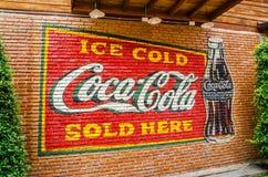 Klassiskt varumärke som brännmärker logo av cocaen - cola på väggen för röd tegelsten arkivbild