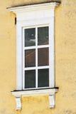 Klassiskt vitt fönster i en gul vägg arkivbilder