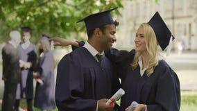 Klasskompisar i avläggande av examen utrustar samtal, att krama och att gratulera sig arkivfilmer