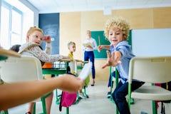 klasskompisar som passerar meddelandet under kurs medan se för lärare arkivbild
