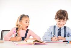 Klasskompisar som sitter på tabellen och tillsammans studerar arkivfoto