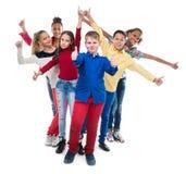 Klasskompisar som står med deras händer och tummar arkivfoton
