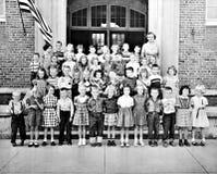 Klassrum av ungar och en lärare framme av byggnad Arkivbild