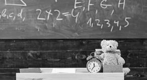 Klassrum med den svart tavlan på bakgrund Barnsligt skrivbord med ringklockan och nallebjörnen Grundskola för barn mellan 5 och 1 arkivfoton