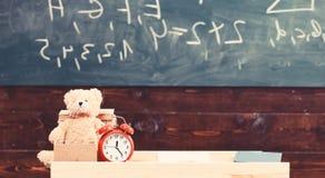 Klassrum med den svart tavlan på bakgrund Barnsligt skrivbord med ringklockan och nallebjörnen Grundskola för barn mellan 5 och 1 arkivbilder