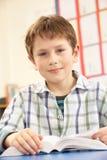 klassrumschoolboy som studerar läroboken royaltyfria bilder