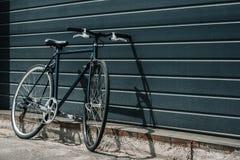 Klasycznego modnisia czerni rowerowa trwanie pobliska ściana outdoors Zdjęcie Stock