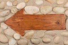 Klasyczni drewniani strzała i bielu kamienie na piasku obraz royalty free