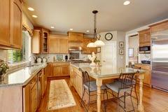 Klasyczny Amerykański kuchenny inerior z brown gabinetami i granitu odpierającym wierzchołkiem Zdjęcie Stock