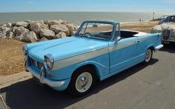 Klasyczny bławy Triumph Herald otwarty odgórny motorowy samochód parkujący na nadbrzeże deptaku Zdjęcia Royalty Free