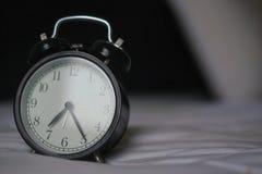 Klasyczny budzik na łóżku Zdjęcie Stock