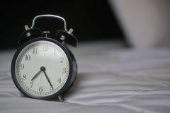 Klasyczny budzik na łóżku Zdjęcie Royalty Free