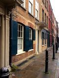 Klasyczny europejski budynek w angielskim sposobie z żaluzjami na grodzkiej ulicie po deszczu Obrazy Royalty Free