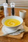 Klasyk Pureed Dyniowa Zupna polewa z mlekiem, śmietanką i pieprzem, Słuzyć na drewnianym talerzu z solą, czosnkiem i cutlery, zdjęcia royalty free