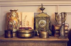 Klatka piersiowa kreślarzi, pułk z antycznymi rzeczami Antyczny zegar, waza Fotografia Stock