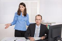 Klatsch und Belästigung unter Geschäftsleuten auf Arbeitsplatz - criti Lizenzfreies Stockbild