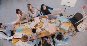 Klatschen die jungen glücklichen Teilhaber der Draufsicht, die am modernen Bürotisch sich treffen, das Feiern des schönen weib stock video