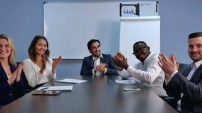 Klatschende Hände des erfüllten stolzen Geschäftsteams und Betrachten der Kamera in einem modernen Büro stock video