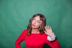 Klatschkonzept Buntes Studioporträt der hübschen jungen Frau mit Palme nahe ihrem Ohr hübsche Frau in den roten Kleidergriffen stockbilder