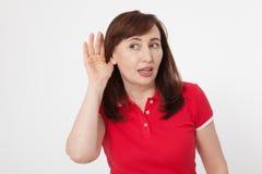Klatschkonzept Porträt der recht mittleren Greisin mit Palme nahe ihrem Ohr Rotes leeres Polohemd Kopieren Sie Platz lizenzfreie stockfotografie