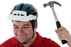 Klatscht ist Hammer auf einem Sturzhelm Stockfotografie
