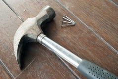 Klauwhamer en spijkers op houtbevloering Stock Afbeeldingen