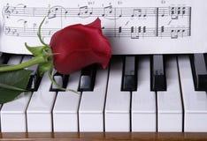Klavier mit roter Rose Lizenzfreie Stockbilder