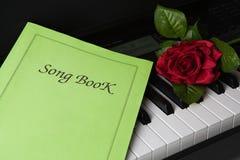 Klavierschlüssel, Liedbuch und rosafarbene Blume Lizenzfreies Stockbild