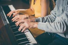 Klavierspieler, die zusammen vier-übergeben spielen Stockfoto