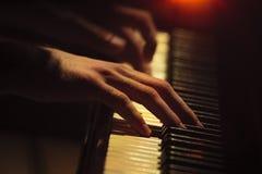 Klavierspielerhände auf der Tastatur Stockfotografie
