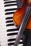 Klaviertastatur, alte Violine und Eheringe Stockbild