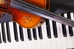 Klaviertastatur, alte Violine und Eheringe Stockbilder