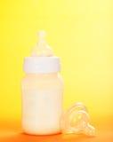 Klaxon avec du lait et une tétine Photographie stock libre de droits