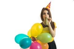 Klaxon de soufflement de jeune fille élégante avec des ballons dans des ses mains sur la fête d'anniversaire Photographie stock