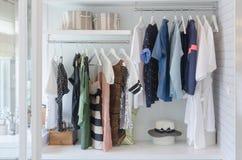 Kläder som hänger i garderob med hatten Arkivfoto