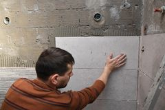Kleben von Fliesen auf der Wand Legen von Fliesen auf die Wand lizenzfreie stockbilder