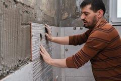 Kleben von Fliesen auf der Wand Legen von Fliesen auf die Wand lizenzfreie stockfotografie