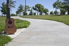 Kleber-Gehweg mit der Gitarre, die gegen ein Ligh stillsteht Stockfotografie
