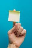 Klebrige Anmerkung, Finger oben des Daumens, gelbe Anzeige auf blauem Hintergrund Lizenzfreie Stockfotografie