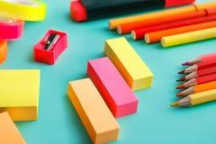 Klebrige Anmerkungen, Bleistiftspitzer, färbten Bleistifte und bunte Markierungen Stockfotografie