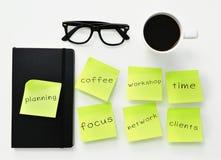 Klebrige Anmerkungen mit verschiedenen Arbeitskonzepten auf einem Schreibtisch Lizenzfreies Stockbild