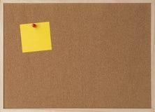 Klebrige gelbe Anmerkung über Holzrahmenkorkenbrett Stockbild
