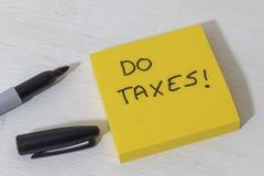 Klebriger Notizblock mit der Anzeige, zum von Steuern zu tun Stockfotografie