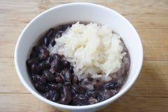 Klebriger Reis und schwarze Bohnen mit Kokosmilch auf hölzernem Hintergrund, thailändischer Nachtisch stockfotos