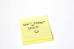 Klebriges Anmerkungspost-it, vergessen nicht zu lächeln, lokalisiert Stockfoto