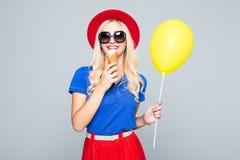 Kleden de manier gelukkige glimlachende vrouw zich met gele luchtballon en de roomijskegel die strohoed en kleur dragen over grij royalty-vrije stock foto's